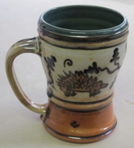 "decorated mug with hedgehog & oak tree design; 4.5 – 5"" tall."